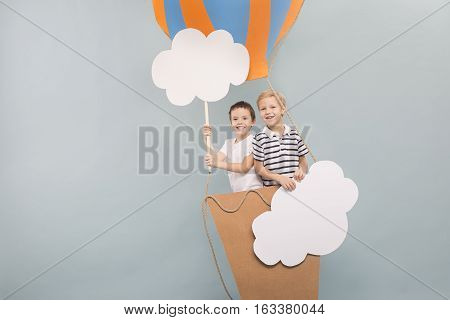 Friends flying in air balloon among clouds