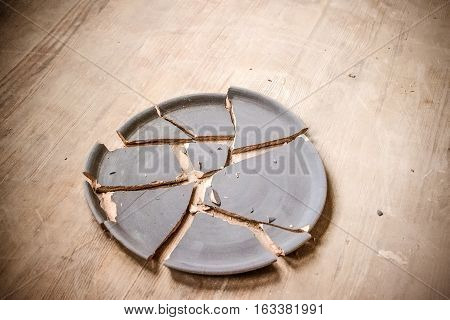 broken clay plate lying on a wooden table