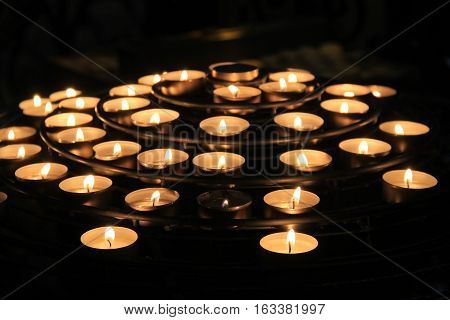 Grouping of several candles, lit against the darkness in remembrance of lost loved ones