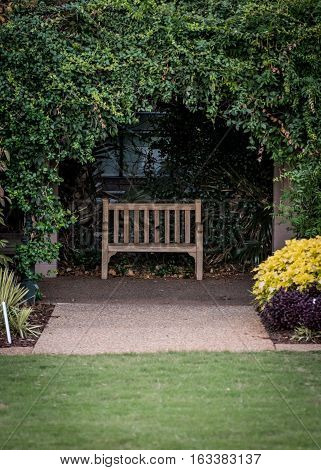 Small Park Bench in Ivy Alcove behind green lawn