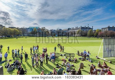 Students and teachers outdoors. Trinity College, Dublin, Ireland - April 23, 2016: Students and teachers outdoors on Campus ground at cricket field. College students and teachers, Campus ground.