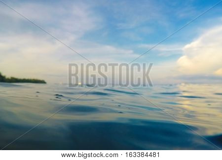 Water background with waterline cloudy sky tropical island. Double landscape with sea and sky. Water line background. Tropical island seaside. Sunset sky with orange clouds. Romantic holiday