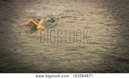 swimmer wear the yellow bathing cap on the left side of picture. and swim straight to his destination with attempting to win speedily (in dark mode)