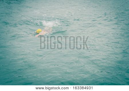 swimmer wear the yellow bathing cap on the left side of picture. and swim straight to his destination with attempting to win speedily