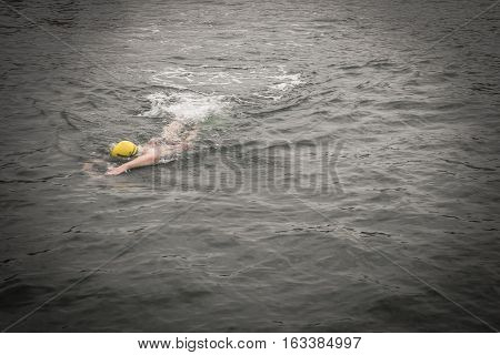 swimmer wear the yellow bathing cap on the left side of picture. and swim straight to his destination with attempting to win speedily (in the dark mode)