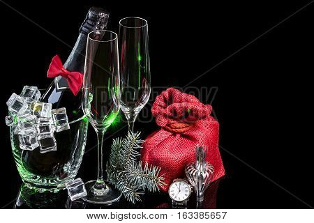 Bottle of champagne in an ice bucket with wineglasses and gift and watches