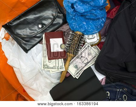 Crumpled clothes cellophane bags cash and passport in mess. Overhead shot concept of travel