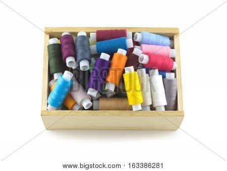 Lot of colored thread spools in wooden box isolated over white closeup