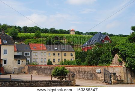 Schengen, Luxembourg - July 11, 2014. Street view in Schengen, with buildings and steeply rising hillside banks of the Moselle River covered with vineyards.