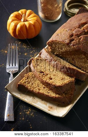 Sliced pumpkin bread loaf dusted with cinnamon