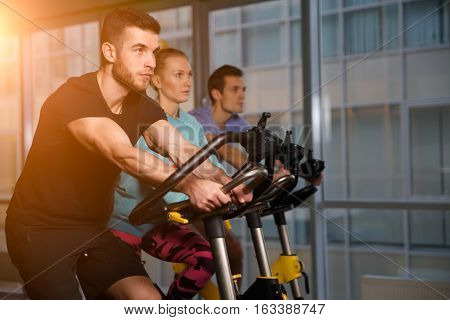 Sports people on stationary bike in top form in gym