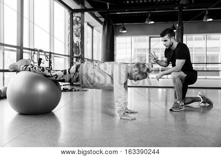 Black-white picture of workout girl on fitball in gym
