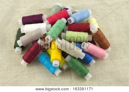 Lot of color thread spools on beige fabric close up