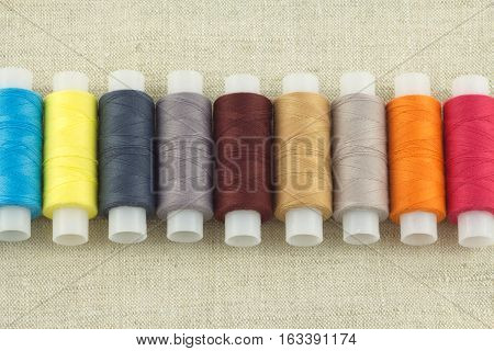 Row of color threads spools on beige fabric close up horizontal view