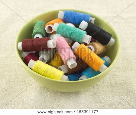 Lot of color thread spools in round green bowl on beige fabric close up