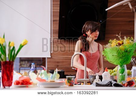 Woman In The Kitchen Washing Dishes