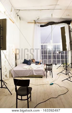 Backstage concept. Multiple equipment for photo production of modern studio. Backstage picture of bedroom during photo session.