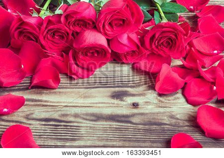 red roses in a bouquet and the scattered petals on a wooden brown background