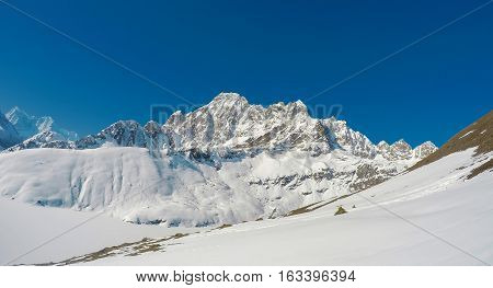 Mountain landscape with rocky ice peaks of Sagarmatha National Park. Severe Nepal winter. Blue sky and white snow double landscape. Himalaya traveling and extreme sport. Outdoor trekking
