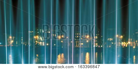 AMSTERDAM, NORTH HOLLAND/THE NETHERLANDS - DECEMBER 3, 2016: View of  Prins Hendrikkade through the illuminated fountain during the Light Festival