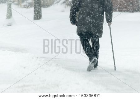 person walking with cane in snow storm on city streets with snow falling