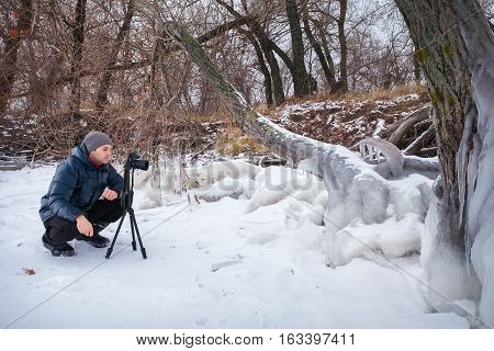 Professional on the lake. Nature photographer takes photos with mirror camera on the coast of lake in winter season.