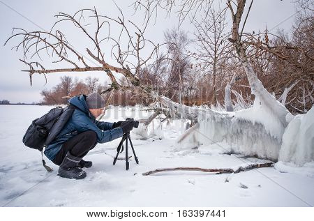 Professional on the lake. Nature photographer takes photos with mirror camera on the lake in winter season.