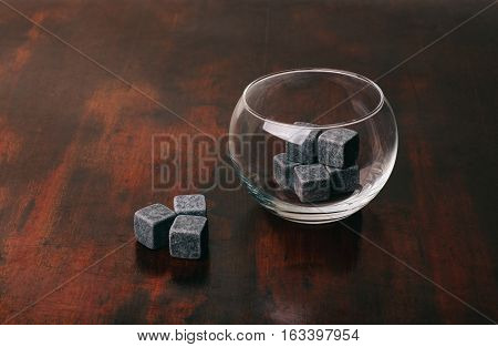Whisky stones with a glass on a surface from mahogany