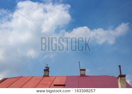 not finished painting red roof against the sky in summer