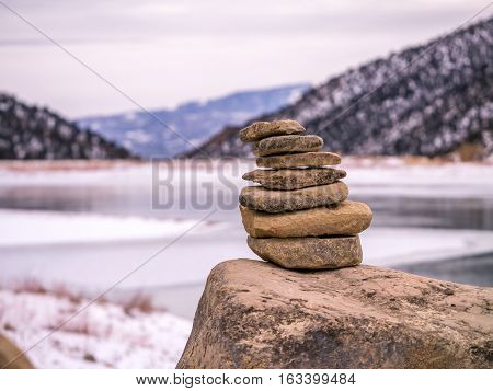 Isolated Rock Cairn With Frozen Lake Background