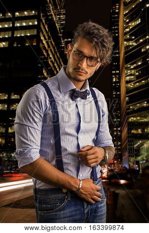 Portrait of brunette young man in glasses, bow-tie, suspenders and shirt on dark smoky city street. Vintage look