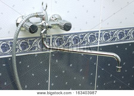 Water taps with hot and cold water close up in bathroom decorated with tiles