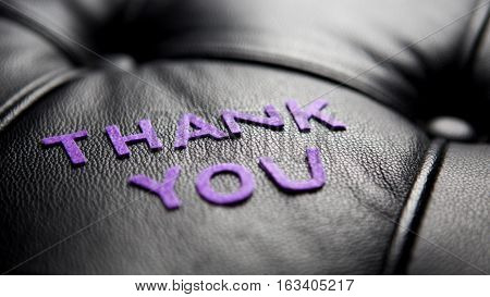 the word Thank You in purple on black leather