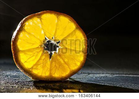 tangerine slice on wooden background back lighted