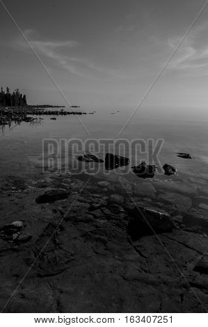 Dead calm afternoon image of clear lake huron water and limestone rocks along shoreline. Clouds reflecting in a zign zag. b/w