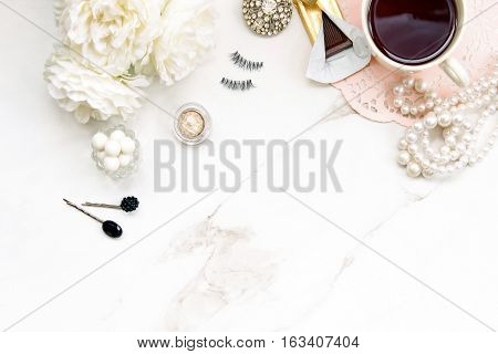 White elegant make up table with coffee, chocolate, jewelry and make up.