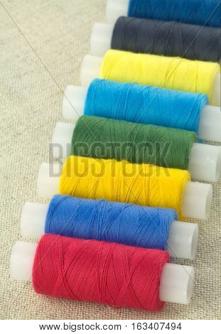 Row of color threads spools on beige fabric diagonal view close up
