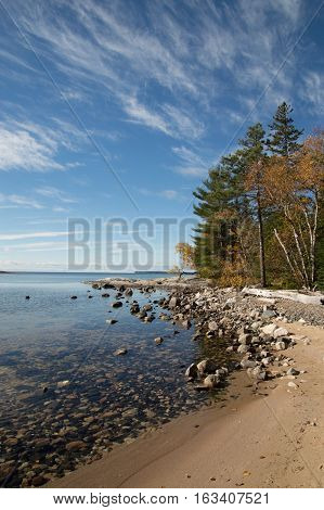 Katherine cove and the oines there inspired the group of seven artists. Image shows dead calm clear lake with rocks sandy beach and fall trees. Blue sky with dircetional cirrus clouds