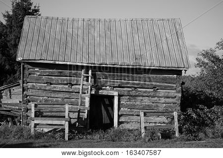 This black and white image of a sawn log cabin with a door and tin roof show the long side of the building.