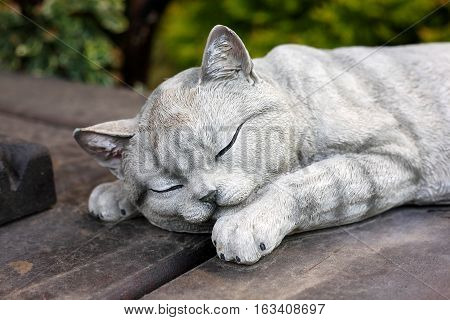 Figurines - A figure of the sleeping cat on a wooden floor and a green background.