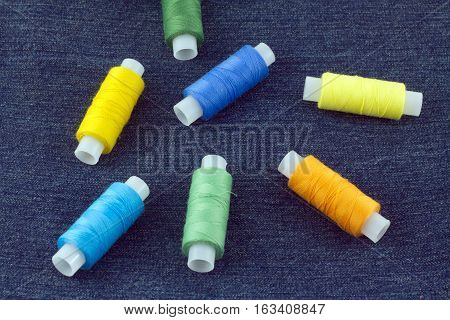 Spools with color threads on blue jeans fabric background close up