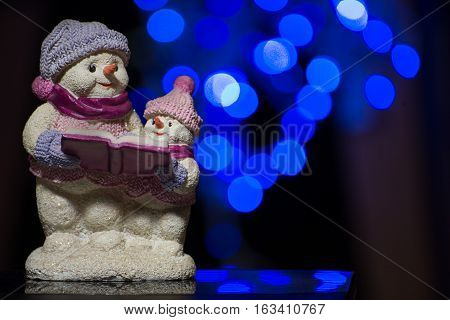 Portrait of two snowmen figurines reading a book on bokeh background