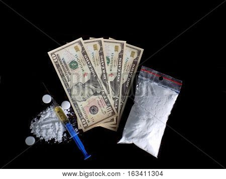 Cocaine drug powder pile and bag, injection syringe and pills and dollar money bills on black background