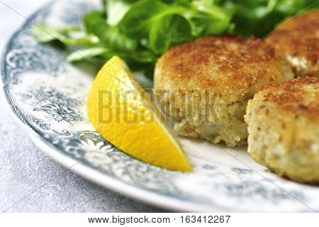 Fish Cutlets With Cream Sauce On A Vintage Plate.top View.