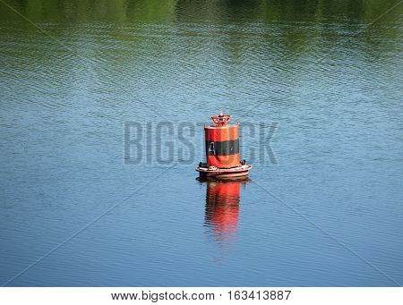 Old red buoy on quiet river with holidaymakers on it ducks on summer day