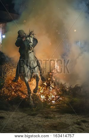 Men rides his horses through the fire in the traditional celebration of Saint Anthony's day in the small village of San Bartolome de Pinares in Spain
