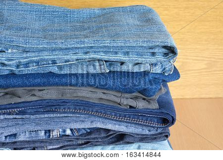 Stack on many cotton jeans isolated on white background close-up