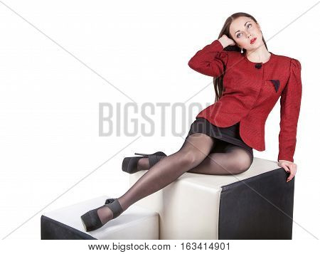 Leggy young pretty woman dressed in red jacket and mini skirt sitting in studio looking up isolated on white background free space for text
