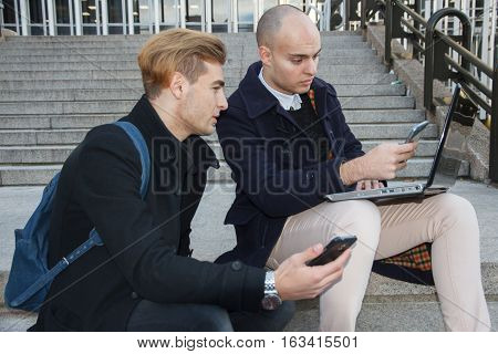 Two young business men, one bald and the other with blond hair working with a laptop and the smart phone on some stairs in the city - technology, business, work concept