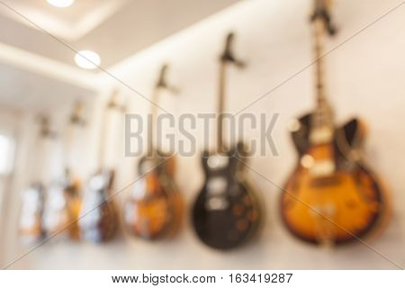 Blur abstract background with guitars hanging on white wall, stock photo